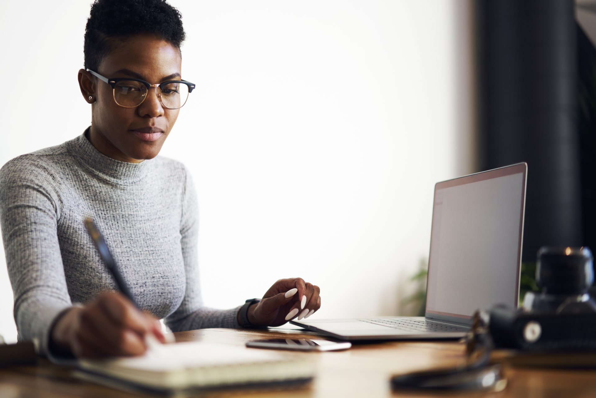 business insights Africa, Pensive prosperous afro american graphic designer concentrated on creating blueprint drawing sketch, skilled copywriter noting ideas for advertising campaign sitting near laptop with blank screen